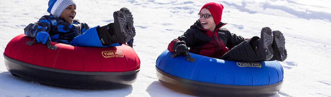 Boys sledding down a winter hill